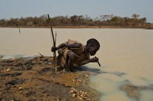 Un niño pastor bebe a través de un filtro de agua en Terekeka (Sudán del Sur)