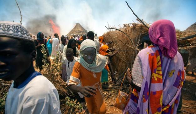 Refugiados huyen de las llamas en un campamento de Darfur.