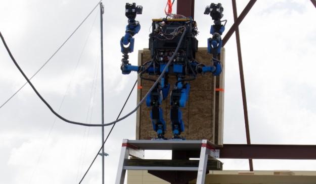 El equipo de SCHAFT levanta los brazos del robot en señal de victoria