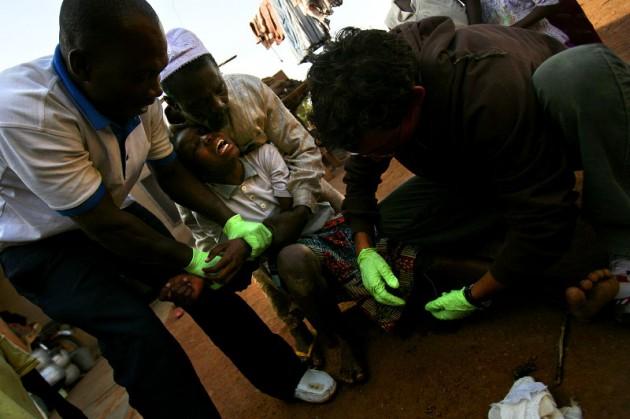 Trabajadores sanitarios extraen un gusano de la pierna de una niña en Ghana
