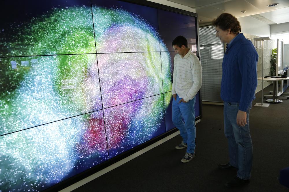Kai, con su padre, frente a una imagen del cerebro en 3D.
