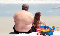 Un hombre obeso descansa en una playa con una bebida azucarada