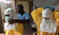 Personal médico preparándose para trabajar en un centro de respuesta contra el ébola con el traje protector.