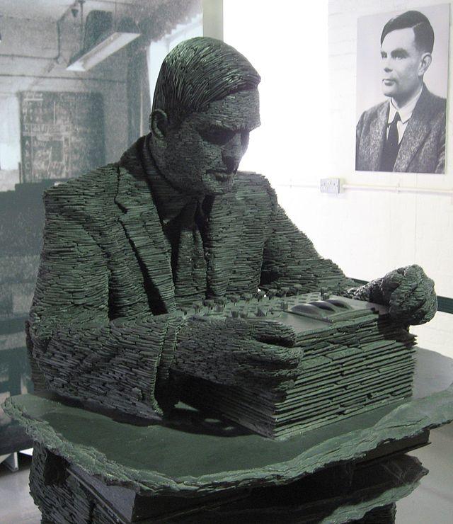 Una estatua de Alan Turing, con su retrato detrás.